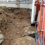 Excavator digging up wall